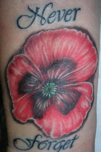 Red poppy with writings tattoo on wrist