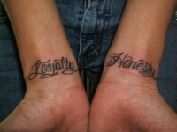 calligraphic tattoo on both wrists